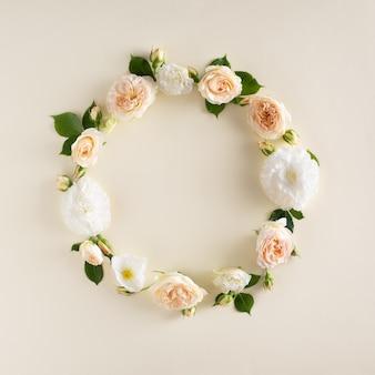 Sommerkranz aus rosen und blättern auf cremefarbenem hintergrund. natürliches rundes rahmenlayout. flache lage, ansicht von oben.