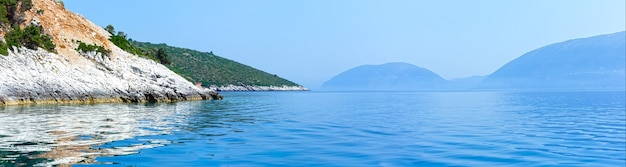 Sommerküstenansicht vom motorboot (kefalonia, nicht weit von agia effimia, griechenland) und von der insel ithaka auf der rechten seite. panorama.