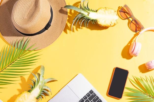 Sommerkulisse mit seggenhut, laptop, telefon und ananas auf gelbem sommerhintergrund