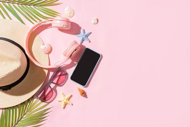 Sommerkulisse mit seggenhut, laptop, telefon und palmblatt auf rosa hintergrund