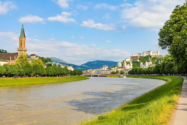 Sommerlandschaft einer europäischen stadt. gebirgsfluss, berge, kirche und festung. salzburg, hohensalzburg