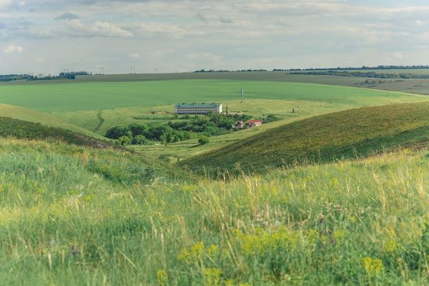 Sommerlandschaft mit den hügeln und schluchten überwältigt mit gras und blauem himmel mit wolken