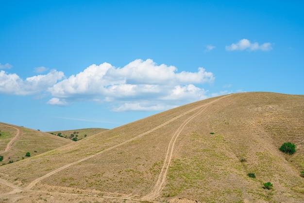 Sommerlandschaft mit wiesen auf den bergen und blauem himmel mit wolken