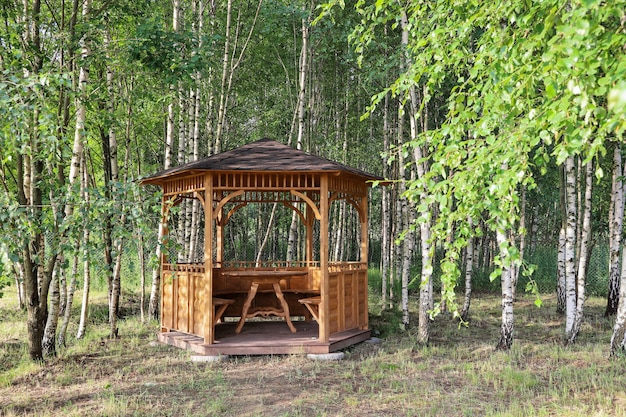 Sommerlaube mit offener laube aus holz im birkenhain