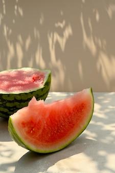 Sommerlebensmittelhintergrund. reife wassermelonenscheibe auf warmem hintergrund mit harten schattierungen und sonnenlicht.