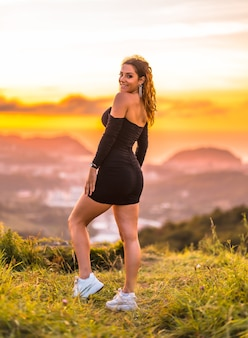 Sommerlebensstil eine junge kaukasische frau mit welligem braunem haar in einem engen schwarzen kleid sehr fröhlich und mit ihren armen oben im sonnenuntergang auf einem berg