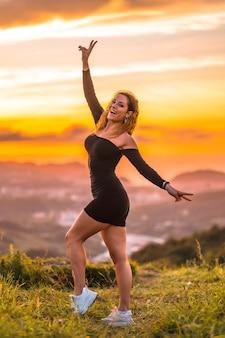 Sommerlebensstil eine junge kaukasische frau mit welligem braunem haar in einem engen schwarzen kleid