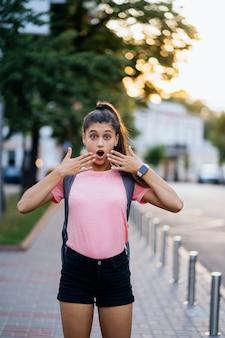 Sommerlebensstil-modeporträt der jungen überraschten frau, die auf der straße geht
