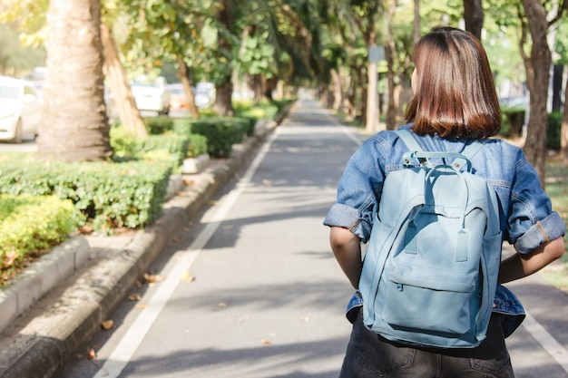 Sommerlebensstilporträt der jungen touristischen asiatischen frau, die auf die straße geht