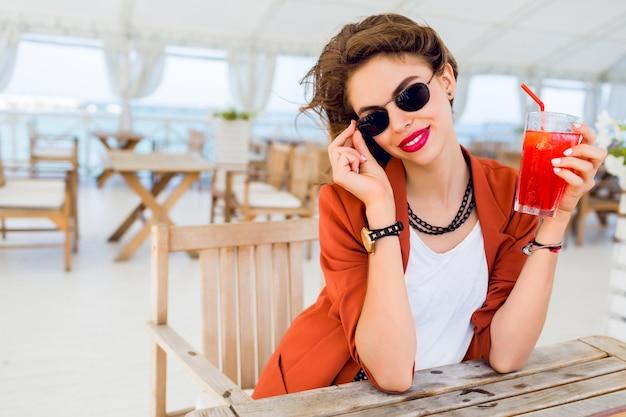 Sommerlebensstilporträt der niedlichen hübschen jungen frau, die im freien aufwirft, im strandcafé sitzt und exotischen cocktail, meereshintergrund trinkt. helle farben. urlaubsstimmung. lächeln und spaß haben.