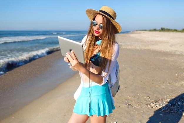 Sommerlebensstilporträt des hübschen blonden mädchens, das am einsamen strand nahe ozean aufwirft, bikinioberteil, hellen rockhut und sonnenbrille tragend hält, kopfhörer und tablette hält