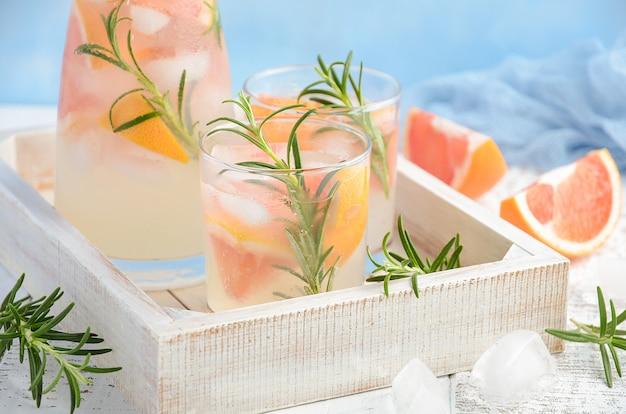 Sommerliches erfrischungsgetränk mit grapefruit und rosmarin.