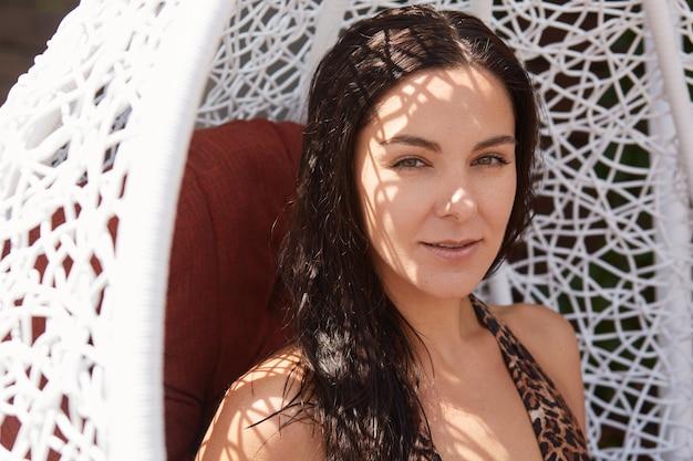 Sommermädchen, das draußen im weißen neststuhl aufwirft. sorglose frau mit dunklem haar, das im schaukelsessel entspannt, attraktive frau, die stilvollen badeanzug, brünette dame trägt