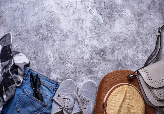 Sommermädchenausstattung auf grauem hintergrund