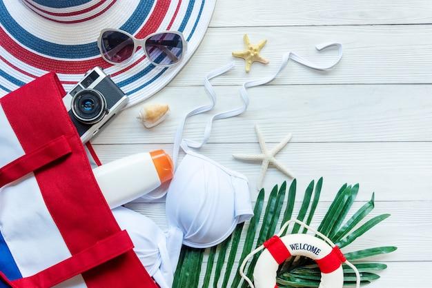 Sommermode-frauenbadeanzug bikini, großer hut und sonnenbrille für reisesommerzeit im strand.