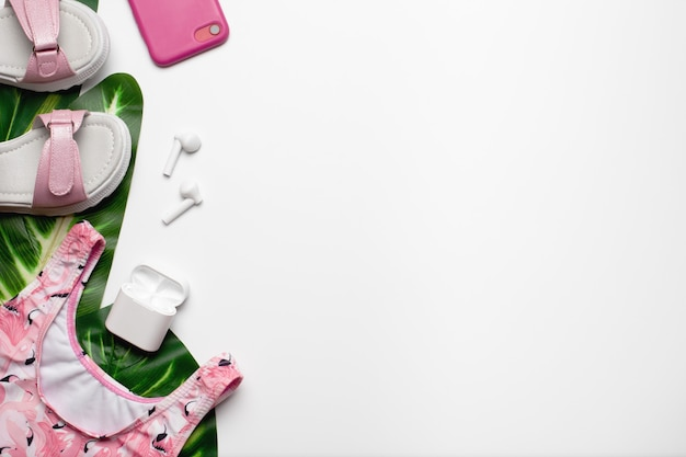 Sommermode mädchen accessoires auf weißem hintergrund mit palmgrünen blättern auf der linken flachen lay top...