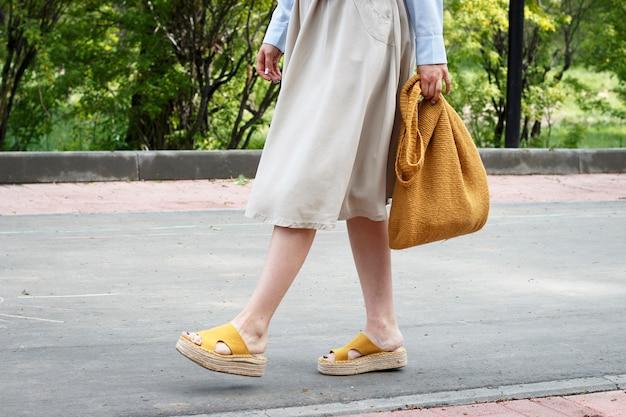Sommermode-outfit. mädchen im kleid, in den gelben schuhen und in der modischen gestrickten tasche, seitenansicht