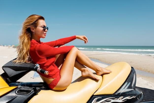 Sommermodefoto der sexy blonden frau in der roten ausstattung, die auf gelbem wasserroller über tropischem strand sitzt.