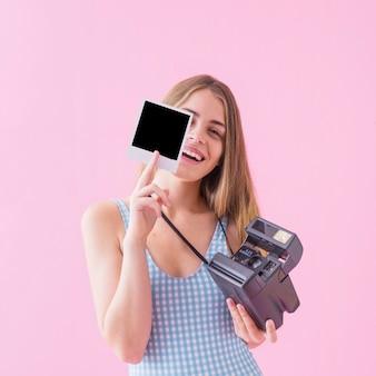 Sommermodekonzept mit der frau, die polaroid zeigt