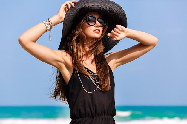 Sommermodeporträt der schönen frau genießen windigen sonnigen tag nahe ozean, urlaubsstil. junges stilvolles mädchen, das schwarzen strampler-weinlesehut und große sonnenbrille, helle farben, freiheit, glück trägt