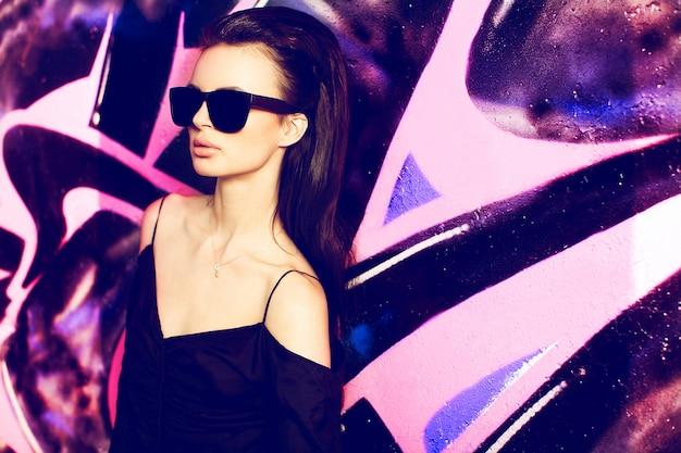 Sommermodeporträt des sexy mädchens im freien. yong schönes weibliches modell im glas, schwarzes t-shirt im extremen park