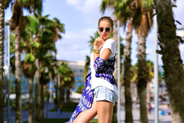 Sommermodeporträt im freien der stilvollen frau, die nahe palmen aufwirft, genießen exotischen urlaub, lässiges outfit, stiefel und sonnenbrille, leuchtende farben, reisen in barcelona, leuchtende farben, straßenstil.