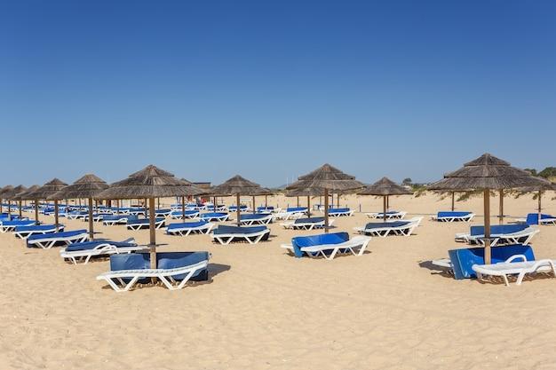 Sommermorgen am algarve strand. sonnenliegen auf sand.