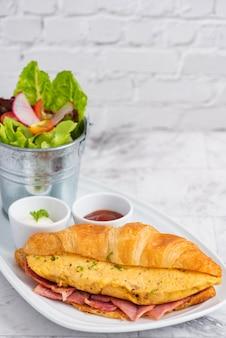 Sommermorgen frühstück croissant gefüllte rühreier mit blumen verziert.