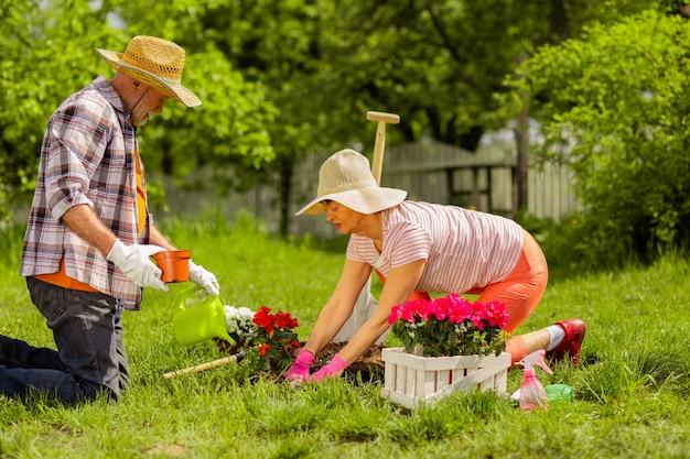 Sommermützen tragen. ehepaar im ruhestand mit sommerhüten, die zusammen blumen in der nähe des hauses pflanzen