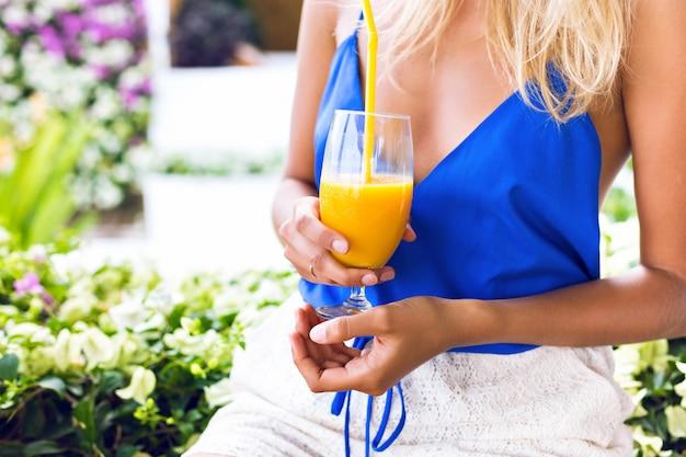 Sommernahaufnahmebild der frau, die frischen organischen leckeren mango-smoothie hält