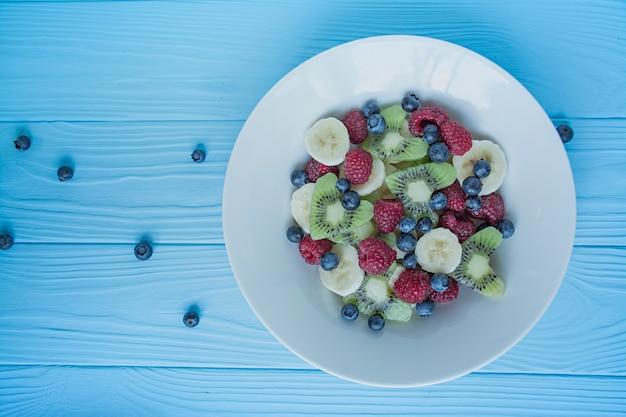 Sommerobstsalat mit kiwi, himbeeren, banane, blaubeeren. vegetarisches gericht. von oben betrachten.