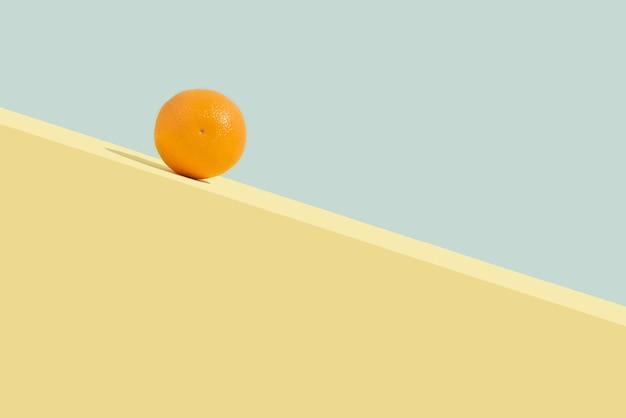 Sommerorangefrucht rollt bergab. auf pastellblauem hintergrund isoliert. abstraktes konzept. rechteckiges layout mit kopienraum.
