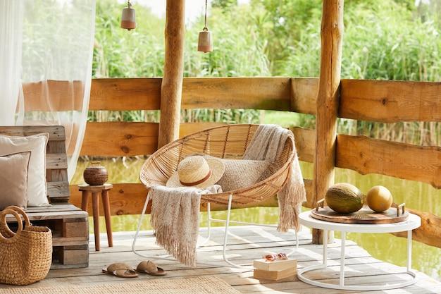Sommerpavillon am see mit stilvollem rattansessel, couchtisch, sofa, kissen, plaid und eleganten accessoires in modernem dekor. sommergefühl. beruhige dich.