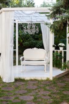 Sommerpavillon mit weißen vorhängen. nische gibt es terrasse, auf der ein weißes sofa im stil der provence oder rustikal.