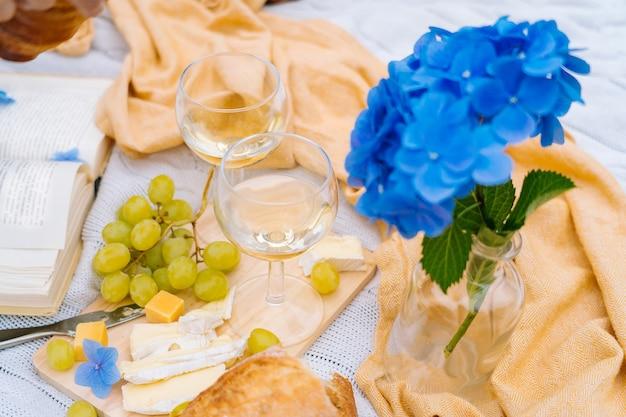 Sommerpicknick an einem sonnigen tag mit brot, obst, blumenstrauß hortensienblumen, gläsern wein, strohhut, buch und ukulele.