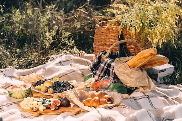 Sommerpicknick bei sonnenuntergang auf dem sonnigen wetter des plaid-, lebensmittel- und getränkekonzeptionslebensstils