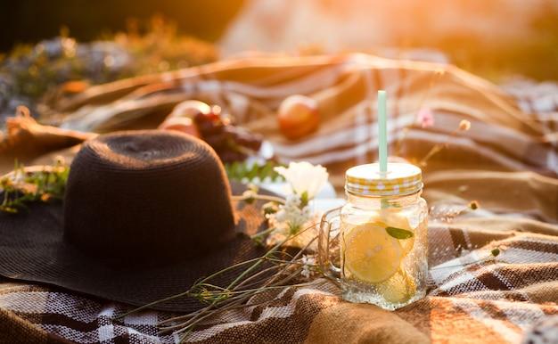 Sommerpicknick draußen, sommergetränkglas mit der limonade, kariert im warmen sonnenlicht