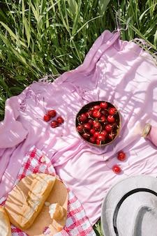 Sommerpicknick ohne abfall auf dem mit kirschen in der hölzernen kokosnussschale