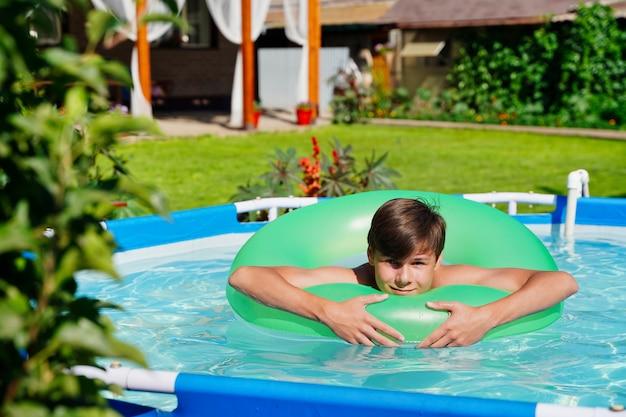 Sommerpool mit grünem kreis und lachendem kerl, der kinder im schwimmbad sonnenbadet, gesättigtes blau ...