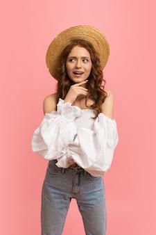 Sommerporträt der fröhlichen rothaarigen dame im modischen outfit, das spaß auf rosa hat