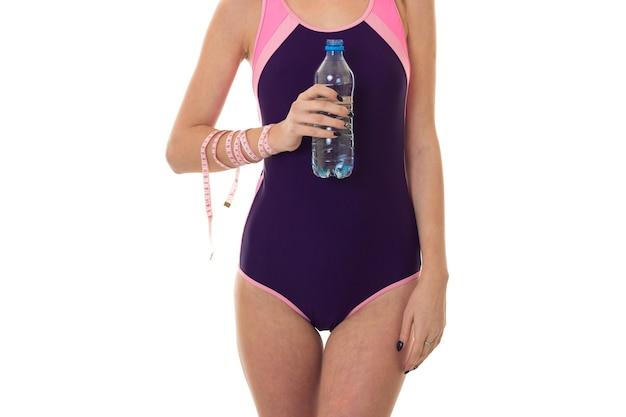 Sommerporträt der jungen dame im badeanzug in voller länge mit flasche und maßband lokalisiert auf weißer wand im studio