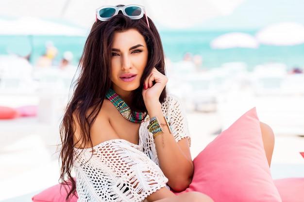 Sommerporträt der schönen brünetten frau, die im strandclub kühlt. tropisches zubehör.