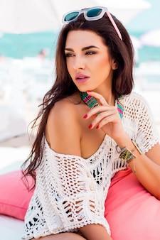 Sommerporträt der schönen brünetten frau, die im strandclub kühlt