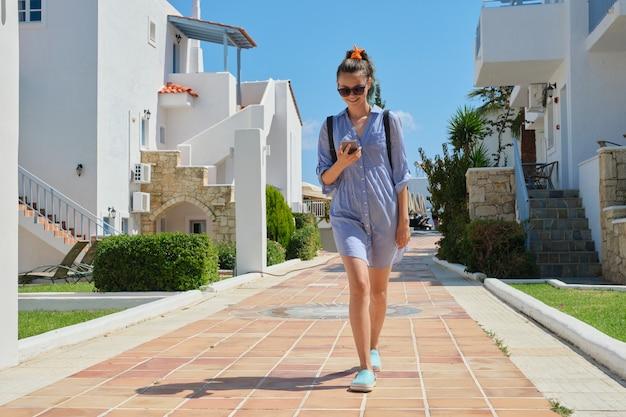 Sommerporträt des laufenden teenager-mädchens mit smartphone