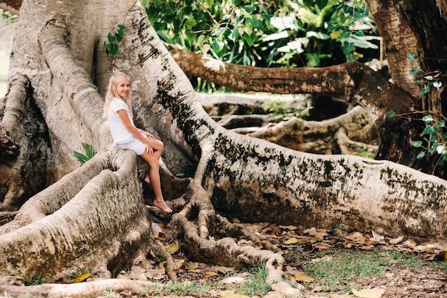 Sommerporträt eines glücklichen kleinen mädchens auf der insel mauritius, das auf einem riesigen baum sitzt. ein mädchen sitzt auf einem großen baum im botanischen garten der insel mauritius.