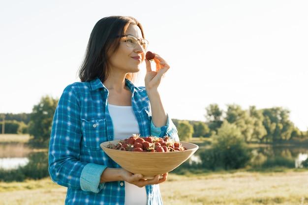 Sommerporträt im freien der erwachsenen frau mit erdbeeren