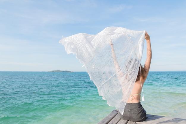 Sommerporträt im freien der jungen hübschen frau, die zum ozean tropischem strand betrachtet