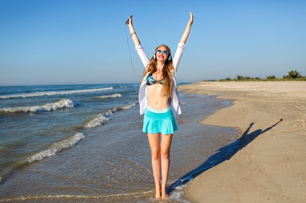 Sommerporträt im freien des glücklichen hübschen mädchens, das spaß hat und in der nähe des ozeans verrückt wird, sonnige farben und positive stimmung, helle trendige strandkleidung, musik über kopfhörer hörend