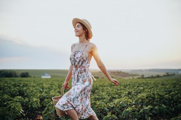 Sommerporträt im freien des jugendlich mädchens mit korberdbeeren, strohhut. ein mädchen auf landstraße, rückansicht. naturhintergrund, ländliche landschaft, grüne wiese, landhausstil