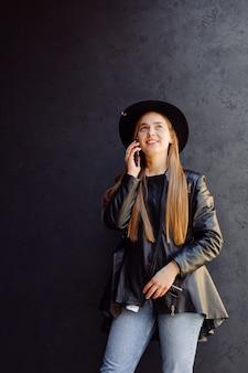Sommerporträt im freien des jungen stilvollen mädchens, das im sonnigen tag auf straße mit telefon aufwirft